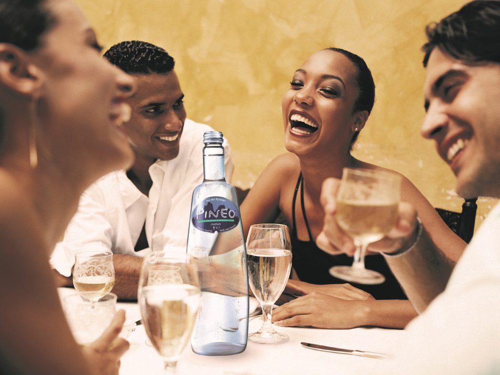 Groep mensen aan tafel op restaurant die genieten van natuurlijk mineraalwater als tafelwater